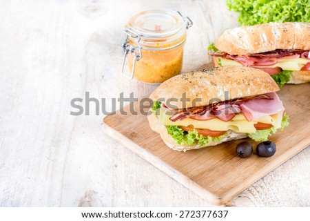 Two ciabatta sandwiches with meat and cheese on wooden board,selective focus and blank space  - stock photo