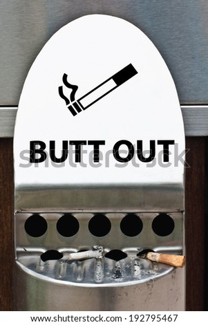 two cigarettes in ash tray with sign Butt Out - stock photo