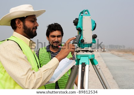 two civil engineers doing a survey on a construction site. Engineers doing land survey at a construction site - stock photo