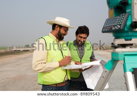 two civil engineers doing a survey on a construction site. engineers doing land survey on site. - stock photo