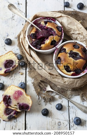 two clafoutis with blueberries and cherries on ceramic ramekins and cake slices on rustic white vintage background with canvas, paper and little forks - stock photo