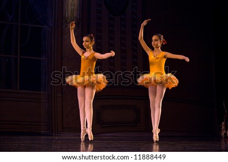 two classic ballet girl dancers in yellow dresses on stage standing with raised hands lit by stage light - stock photo
