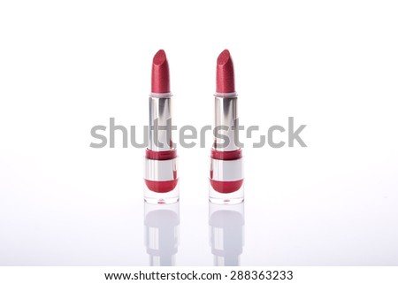 Two classic red lipsticks, studio shot on white background with natural reflection  - stock photo
