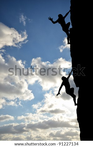 two climber on a steep rock climb to the top against the setting sun - stock photo