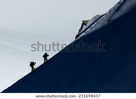 Two climbers on a mountain ridge - stock photo