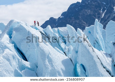 Two climbers reached the top of glacier. Challenging and hostile environment. Several crevices around. Matanuska glacier, Alaska, USA / Two climbers reached the top of glacier - stock photo