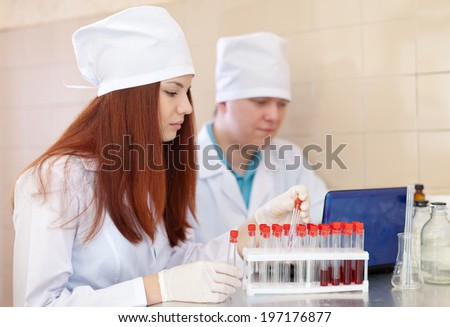 Two clinicians works with blood sample in medical laboratory - stock photo