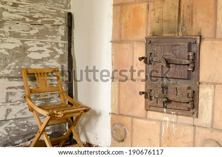 two closed old retro rustic furnace doors with handle and wooden rest chair  - stock photo