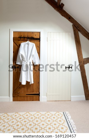 Two closed wooden doors in a loft room.  One is painted white, the other is unpainted and has a bathrobe hanging on a hook. - stock photo