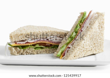 Two club sandwiches served in a plate over white background - stock photo