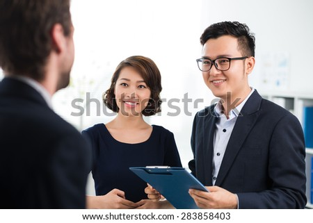 Two co-workers communicating with their new partner - stock photo