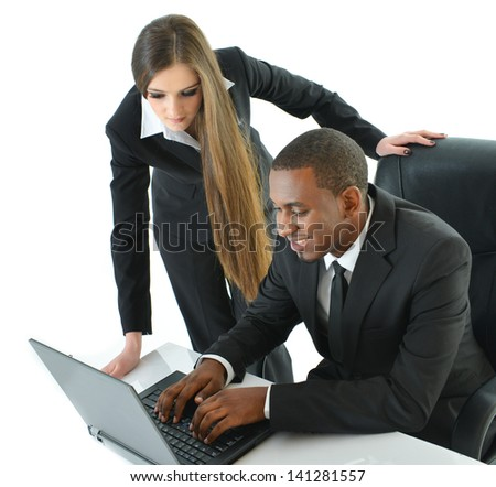 Two Co-Workers working on laptop - stock photo