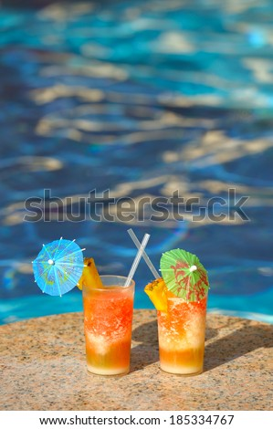 Two cocktail glasses by a blue water of swimming pool  - stock photo