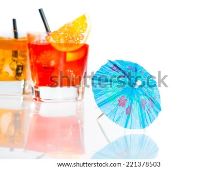 two cocktail with orange slice on top isolated behind blue umbrella on white background with space for text - stock photo