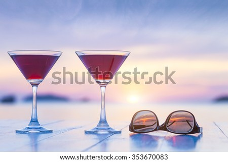 Two cocktails and sunglasses on a table of luxurious tropical beach resort restaurant with beautiful sunset in the background - stock photo