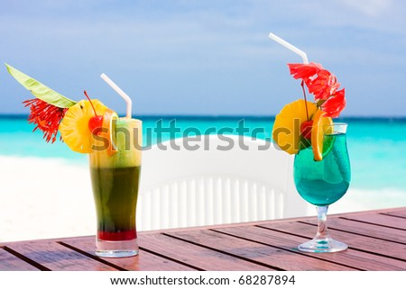 Two cocktails on a table at shore of ocean - stock photo