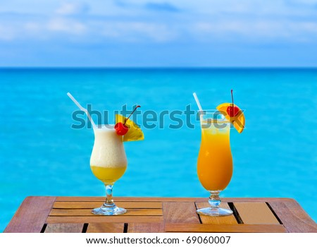 Two cocktails on table, sea background - stock photo