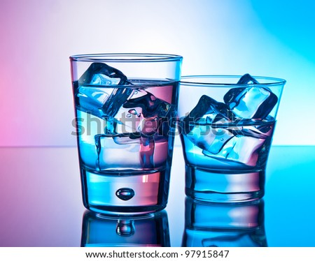 Two cocktails on the rocks on a reflective surface - stock photo