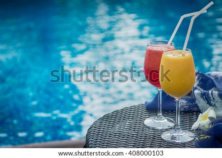 Two cocktails red and yellow on table against blue swimming pool. Travel, luxury, vacation background. Detox healthy drink. Text space - stock photo