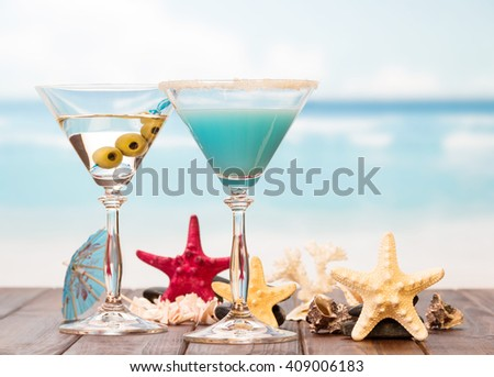 Two cocktails, starfish and sinks on sea background. - stock photo