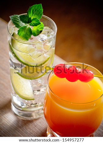 Two cocktails, tequila sunrise and gin and tonic - stock photo
