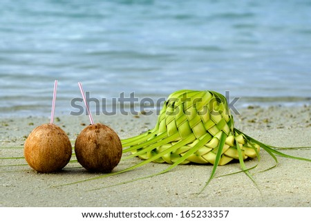 Two coconuts and sun hat knees out of palm leaves on sandy sea shore of tropical island. Concept photo of couples travel ,tourism, love, relationship, honeymoon.  - stock photo