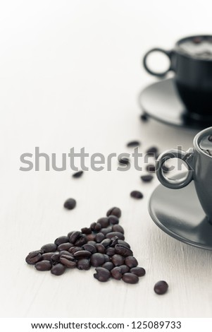 two coffee cup and spilled coffee beans in the shape of heart - stock photo