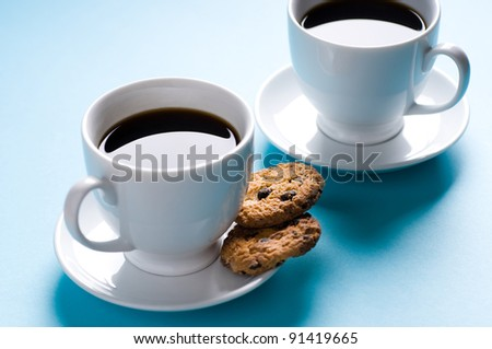 Two coffee cups with cookies on blue background - stock photo