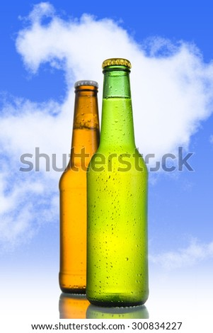 Two Cold frosted beer in green and golden brown bottle frosted and tempting  isolated on a blue sky background in alcoholic refreshing drink concept - stock photo