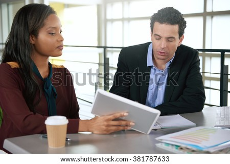 Two  colleages discussing ideas using a tablet  - stock photo