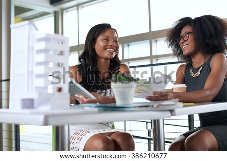 Two  colleages discussing ideas using a tablet computer - stock photo