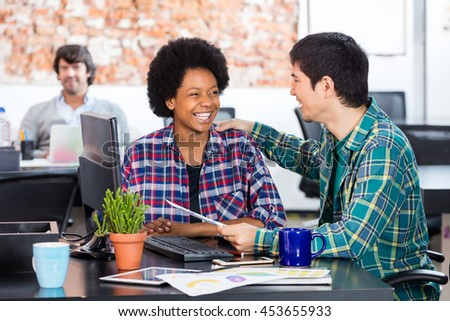 Two colleagues african american woman asian man diverse mix race talking discussing sitting office desk business people working casual wear - stock photo