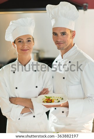 Two colleagues chefs are standing in a professional kitchen presenting a plateful with fine food. They are looking at camera, wearing white chef clothes and hat. Blurred background. - stock photo
