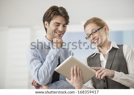 two colleagues discuss around a digital tablet - stock photo