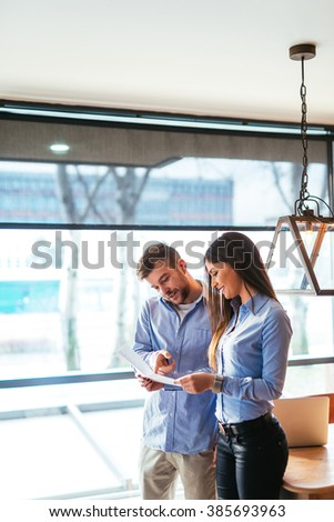 Two colleagues discussing about document in an office. - stock photo
