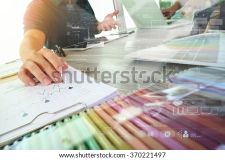 two colleagues interior designer discussing data and digital tablet and computer laptop with sample material and graphics design diagram on wooden desk as concept - stock photo