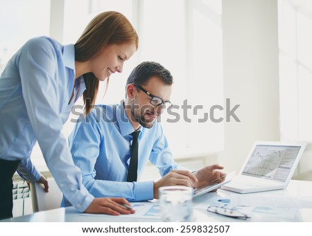 Two colleagues using touchpad - stock photo