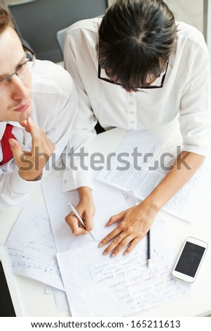 two colleagues working on project together (focus on woman's hands) - stock photo