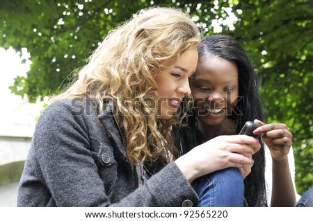Two college friends smiling while reading a text message on a mobile phone. - stock photo