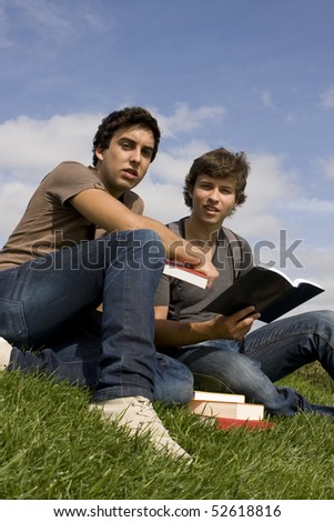 Two college or university students studying on the park - stock photo