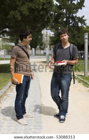 Two college or university students walking on a park path - stock photo
