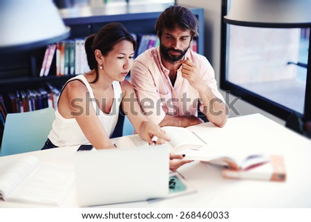 Two college students learning together at university library, brunette asian female and spanish male preparing for exams while sitting at the desk with open books and laptop computer in a study hall - stock photo