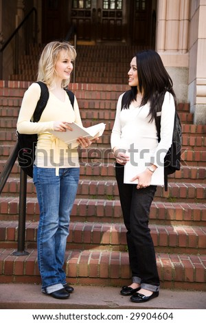Two college students meeting and talking on campus - stock photo