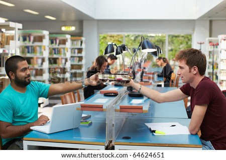 two college students sitting in library with laptop computer and sharing book. Horizontal shape, side view, copy space - stock photo