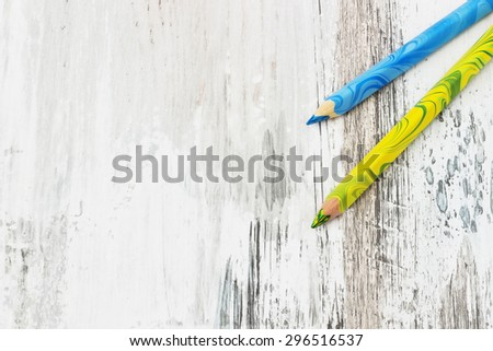 two colored pencil on an old white wooden background. school accessories. copy space background - stock photo