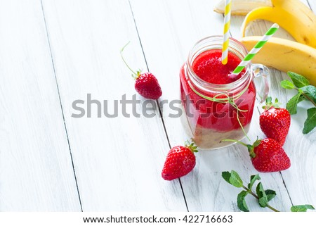 Two colored smoothie with Strawberry and banana in a mason jar at the white table. Strawberry smoothie, summer drink. - stock photo