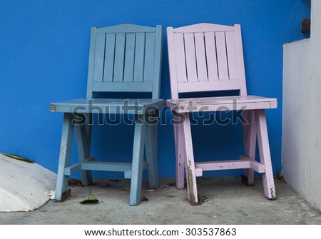 Two colorful chairs on blue wall - stock photo