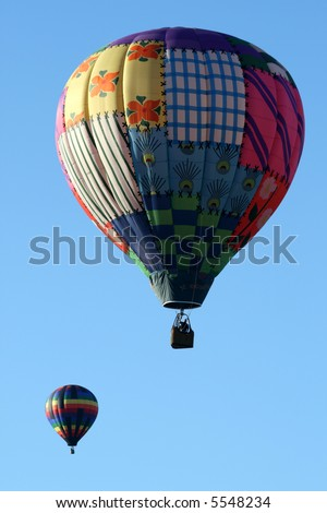 Two colorful hot air balloons during early morning ascend - stock photo