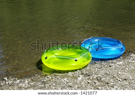 Two colorful inflatable rings for fun at the river - stock photo