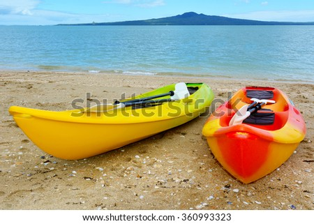 Two colourful empty kayaks on Mission bay beach against Rangitoto Island volcano mountain in Auckland, New Zealand. - stock photo